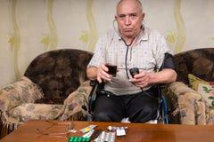 Älterer Mann, der gesunden Saft und BP-Apparat hält lizenzfreie stockfotografie