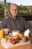 Älterer Mann, der gesundes frühstückt Stockfotografie