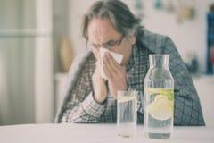 Älterer Mann der Grippe mit Decke lizenzfreie stockfotos