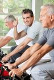 Älterer Mann in der Gymnastikholding greift oben ab Stockfotografie