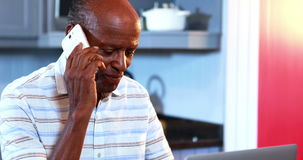 Älterer Mann, der am Handy bei der Anwendung des Laptops spricht stock video