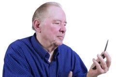 Älterer Mann, der Handy herausfindet Lizenzfreies Stockfoto