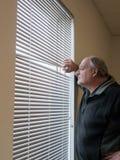 Älterer Mann, der heraus Fenstervorhänge schaut. Lizenzfreie Stockfotos