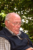 Älterer Mann, der im Garten sitzt Lizenzfreie Stockbilder
