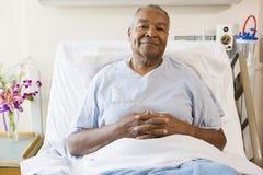 Älterer Mann, der im Krankenhaus-Bett sitzt Stockbild