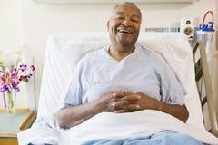 Älterer Mann, der im Krankenhaus-Bett sitzt lizenzfreies stockbild