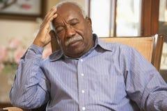 Älterer Mann, der im Lehnsessel sich entspannt Stockfotografie