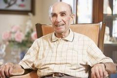 Älterer Mann, der im Lehnsessel stillsteht Lizenzfreie Stockfotografie