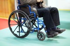 Älterer Mann, der im Rollstuhl sitzt Stockbild