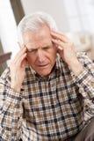 Älterer Mann, der im Stuhl betont schaut Lizenzfreies Stockfoto