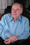 Älterer Mann, der im Stuhl, denkend sitzt Lizenzfreie Stockfotografie