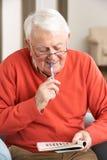 Älterer Mann, der im Stuhl sich entspannt Lizenzfreies Stockbild