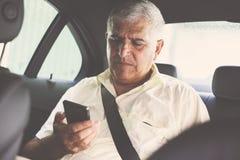 Älterer Mann, der intelligentes Telefon im Taxi verwendet stockfoto