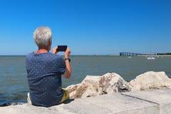 Älterer Mann, der an der Küste sitzt stockfoto