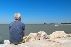 Älterer Mann, der an der Küste sitzt stockfotografie