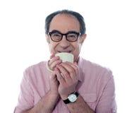 Älterer Mann, der Kaffee lächelt und genießt stockbild