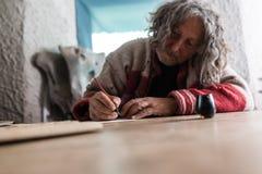 Älterer Mann, der Kalligraphie unter Verwendung eines Spitzenstiftes tut stockbilder