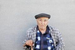 Älterer Mann in der karierten Jacke an der Wand lizenzfreies stockfoto