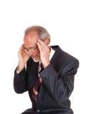 Älterer Mann in der Klage mit Kopfschmerzen Lizenzfreie Stockfotos