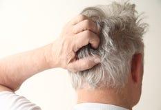 Älterer Mann, der Kopf löscht Stockfotografie