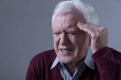Älterer Mann, der Kopfschmerzen hat Stockbild