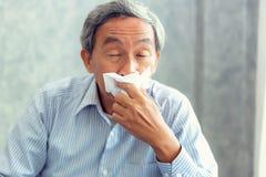 Älterer Mann, der Krankheit hat und in Gewebe, Gesundheitswesen niest stockfotos