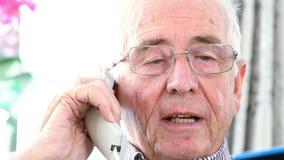 Älterer Mann, der Kreditkarteam Telefon spezifiziert stock footage