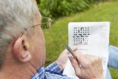 Älterer Mann, der Kreuzworträtsel im Garten tut Stockfoto