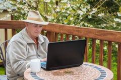 Älterer Mann, der an Laptop-Computer arbeitet Lizenzfreie Stockfotos