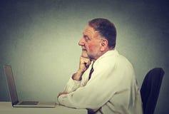 Älterer Mann, der Laptoplesee-mail-Nachrichten verwendet silberne Taste und Laptop-Computer Stockfotos
