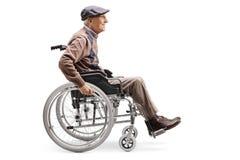 Älterer Mann, der manuell einen Rollstuhl reitet stockbild