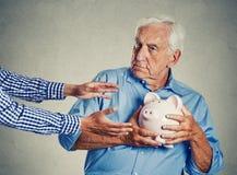 Älterer Mann, der misstrauische schützende Spareinlagen des Sparschweins hält Stockfotos