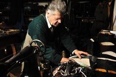 Älterer Mann, der mit alter Maschine arbeitet Stockfotos