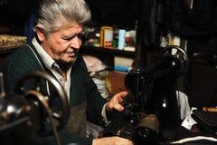 Älterer Mann, der mit alter Maschine arbeitet lizenzfreies stockbild