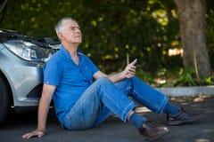 älterer Mann, der mit dem Auto auf Straße nach Zusammenbruch sitzt stockfoto