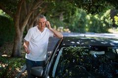 Älterer Mann, der mit dem Auto Telefon verwendet Lizenzfreie Stockbilder