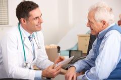 Älterer Mann, der mit einem amerikanischen Doktor spricht