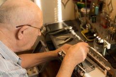 Älterer Mann, der mit einer kleinen Sägemaschine arbeitet Stockbilder
