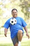 Älterer Mann, der mit Fußball im Park trainiert Lizenzfreie Stockfotos