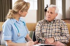 Älterer Mann, der mit Gesundheits-Besucher spricht Stockfotografie