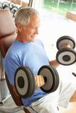 Älterer Mann, der mit Gewichten arbeitet lizenzfreie stockbilder