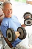 Älterer Mann, der mit Gewichten arbeitet Stockfotografie