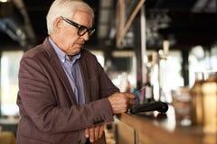Älterer Mann, der mit Kreditkarte zahlt Lizenzfreies Stockfoto