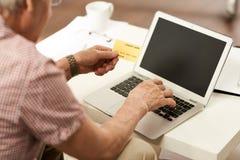 Älterer Mann, der mit Kreditkarte zahlt Stockbilder