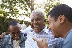 Älterer Mann, der mit seinen erwachsenen Söhnen im Garten, Abschluss oben spricht stockbilder