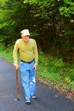 Älterer Mann, der mit Stock geht Stockfoto