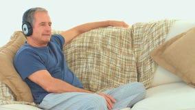 Älterer Mann, der Musik mit Kopfhörern hört stock video