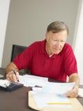 Älterer Mann, der nach Hause Finanzen überprüft lizenzfreie stockfotos