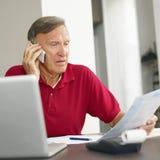 Älterer Mann, der nach Hause Finanzen überprüft stockfotos