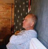 Älterer Mann, der nachdenklich mit den gekreuzten Armen schauend schaut stockfotografie